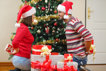 Young couple exchanging Christmas presents in front of the Christmas tree
