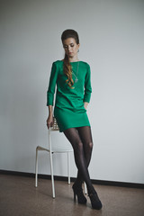 Girl in green dress standing near the chair 4886.
