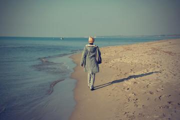 Woman that walks on the seashore in winter