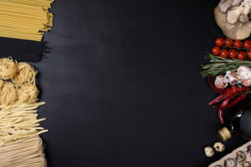 Assorted pasta with eggs, mushrooms, and Italian cuisine ingredients on black wooden background. Top view, copy space.