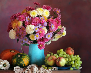 Still life with chrysanthemums, grapes, apples and pumpkins.