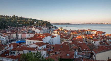 Sunlit Red Roofs of the Town Piran, Slovenia. View from Above at Sunrise.