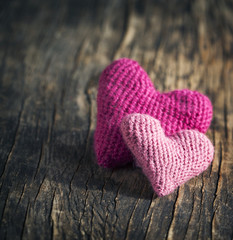 Two crochet pink hearts on wooden background