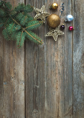 Christmas or New Year rustic wooden background with toy decorations, candy cane and fur tree branch, top view