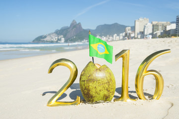 Gold 2016 message with Brazilian flag sticking out from green coco gelado drinking coconut on the beach in Rio de Janeiro, Brazil