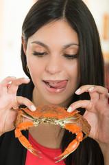Beautiful young girl enjoying a delicious crab