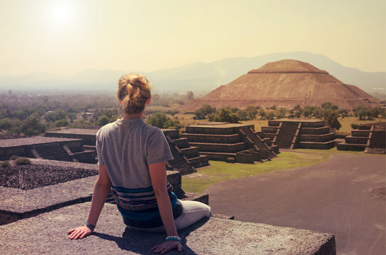 Young woman sitting on the top of pyramid overlooking Teotihuacan
