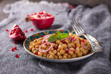 Traditional eastern chickpea salad with pomegranate, red onion and spices