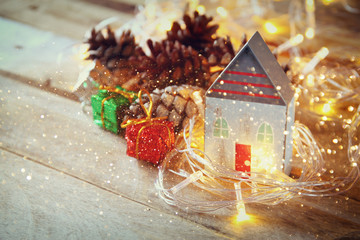 photo of pine cones and decorative wooden house next to gold garland lights on wooden background. copy space. glitter overlay