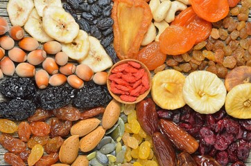 Mix of dried fruits and nuts on a wooden table - symbols of judaic holiday Tu Bishvat. Top view.