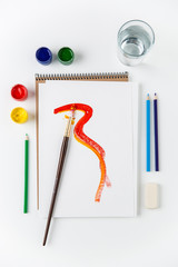 Top view of sketchbook, paintbrush, colorful brushes and pencils
