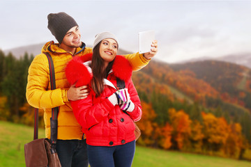 Happy couple with tablet on beautiful mountains background
