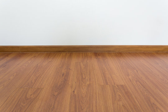 empty room with brown wood laminate floor and white mortar wall