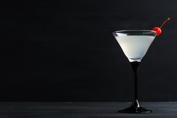 Cocktail in martini glass on the black wooden background