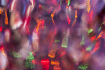 Abstract colorful background. Defocused blurred lights behind a glass surface