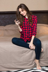 Woman sitting on the bed and using smartphone at home
