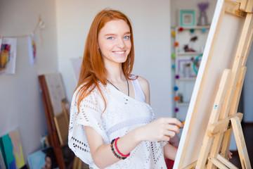 Lovely cute joyful woman artist enjoying drawing in art workshop