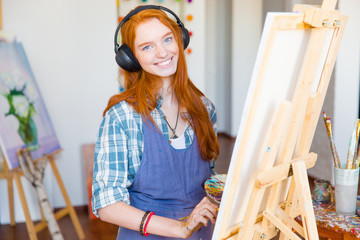 Smiling woman artist painting on canvas and listening to music