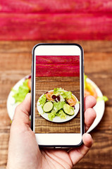 man taking a picture of a salad with his smartphone