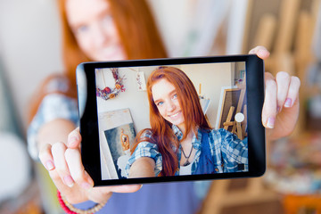 Positive smiling  woman making selfie using tablet in artist workshop