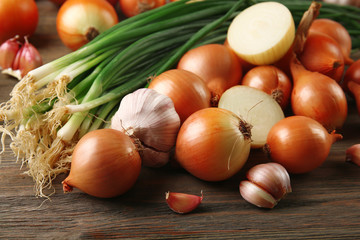 Fresh different onions with garlic on wooden background