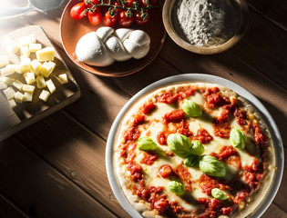 Pizza with tomatoes mozzarella and basil on the wooden table