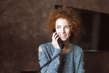 Beautiful happy woman talking on landline telephone in the room