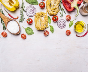 Ingredients for cooking vegetarian pasta with tomatoes, basil, oil, pepper on wooden rustic background top view border ,place for text