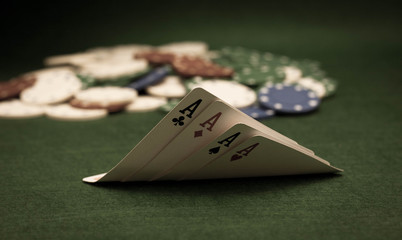 Cards and stack of poker chips and on a green background