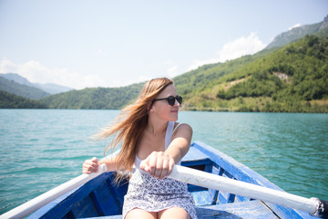 A young woman is rowing a boat on a summer day