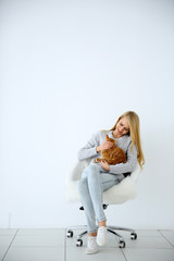 Young woman with red cat sitting on chair against white background