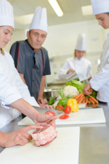 Chef watching student tie joint of meat