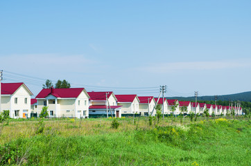 New village of similar houses in  summer sunny day. Russia