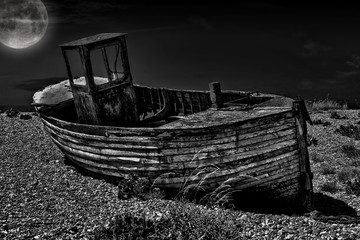 An old abandoned fishing boat stranded on a beech in black and white.