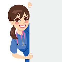 Cute happy young professional nurse peeking out of a blank billboard