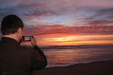 Man with phone on the beach at sunrise, Outer Banks, North Carolina.