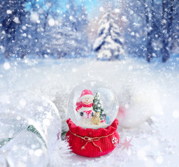 A snow globe with snowman on a background the winter forest
