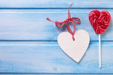 Lollipop heart and decorative heart on blue painted  wooden  pla