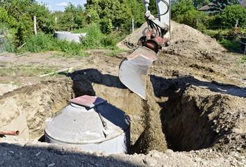 Bagger schüttet Material in Loch mit betonierter Senkgrube