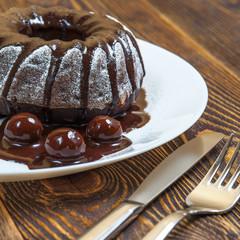 Chocolate cake, three glazed cherry, fork, knife