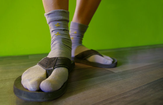 Close up of feet with socks in flip flops