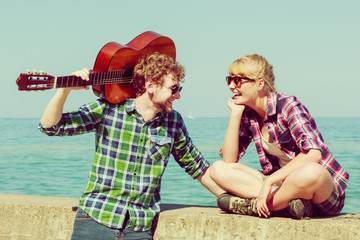 Young man playing guitar to his girlfriend outdoor