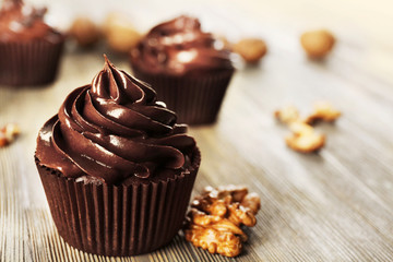 Chocolate cupcakes with nuts on wooden table
