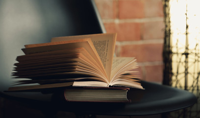 Black modern chair with lamp and books on brick wall background, close up