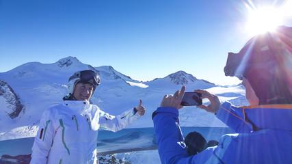 Pärchen im Skiurlaub macht Foto mit Smartphone