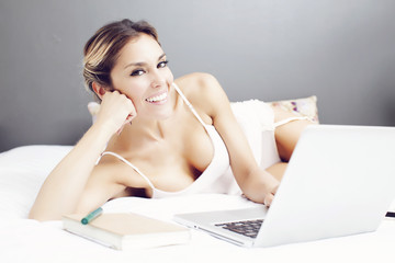 Woman with computer in bed
