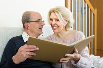 Senior spouses with picture album indoor