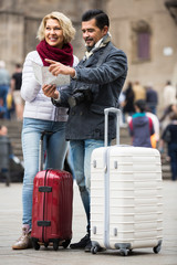 couple with suitcases, camera and map outdoors