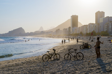Golden sun setting behind a silhouette of the Rio de Janeiro skyline at the Leme end of Copacabana Beach