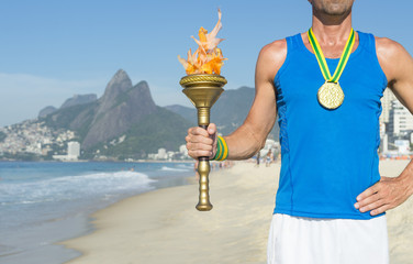 Brazilian gold medal athlete standing with sport torch in front of the skyline at Ipanema Beach in Rio de Janeiro, Brazil